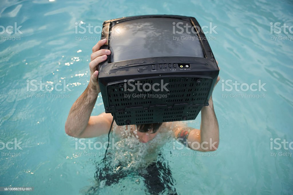 Man in swimming pool with television set royalty free stockfoto