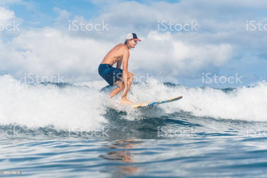 homme en short et une casquette surf dans l'océan de la natation - Photo de Activité de loisirs libre de droits