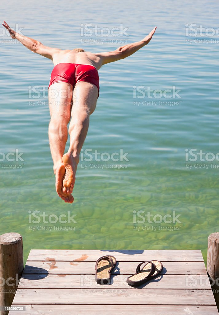 Man in swimsuit jumping into lake stock photo
