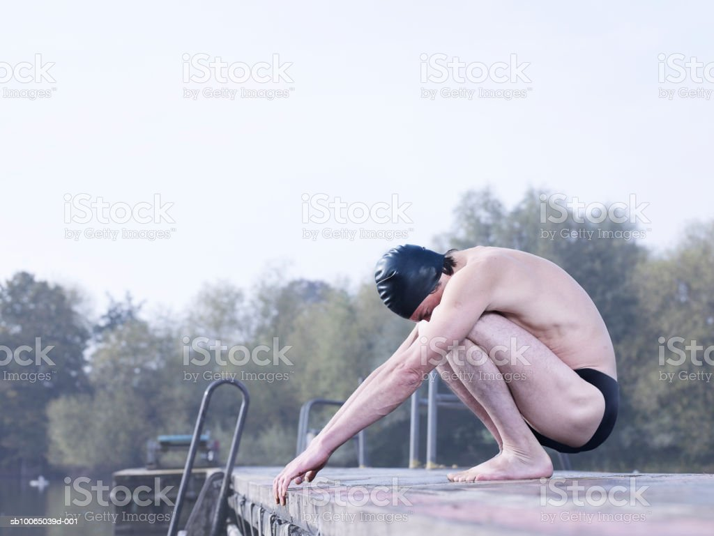 Man in swimwear crouching on jetty foto de stock libre de derechos