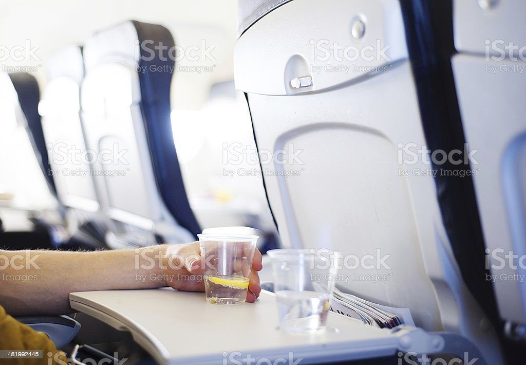 Man in the aircraft is drinking water stock photo