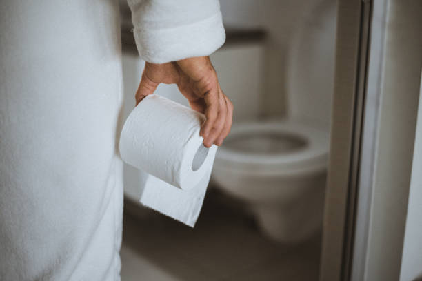 Man in the bathroom holding toilet paper stock photo