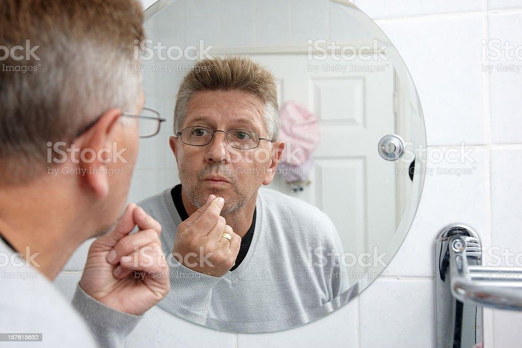Man in the bathroom mirror examining stubble royalty-free stock photo