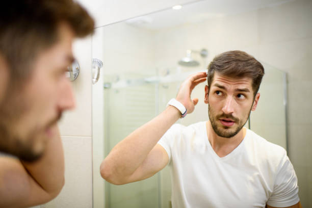 Man in the bathroom Young man in the bathroom looking in the mirror and fixing his hair. dandruff stock pictures, royalty-free photos & images