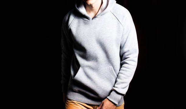 man  in the blank grey hoodie, sweatshirt on a black background, mock up, free space stock photo