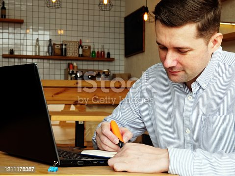 1174436608 istock photo Man in the cafe makes notates in the notepad. 1211178387