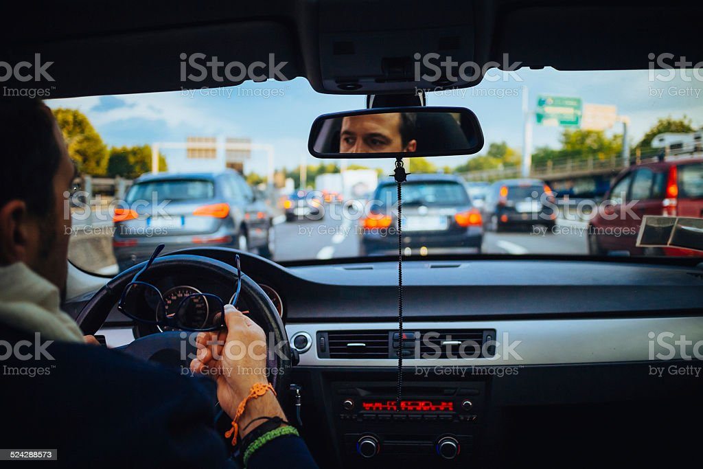 Man in the car during traffic on highway stock photo