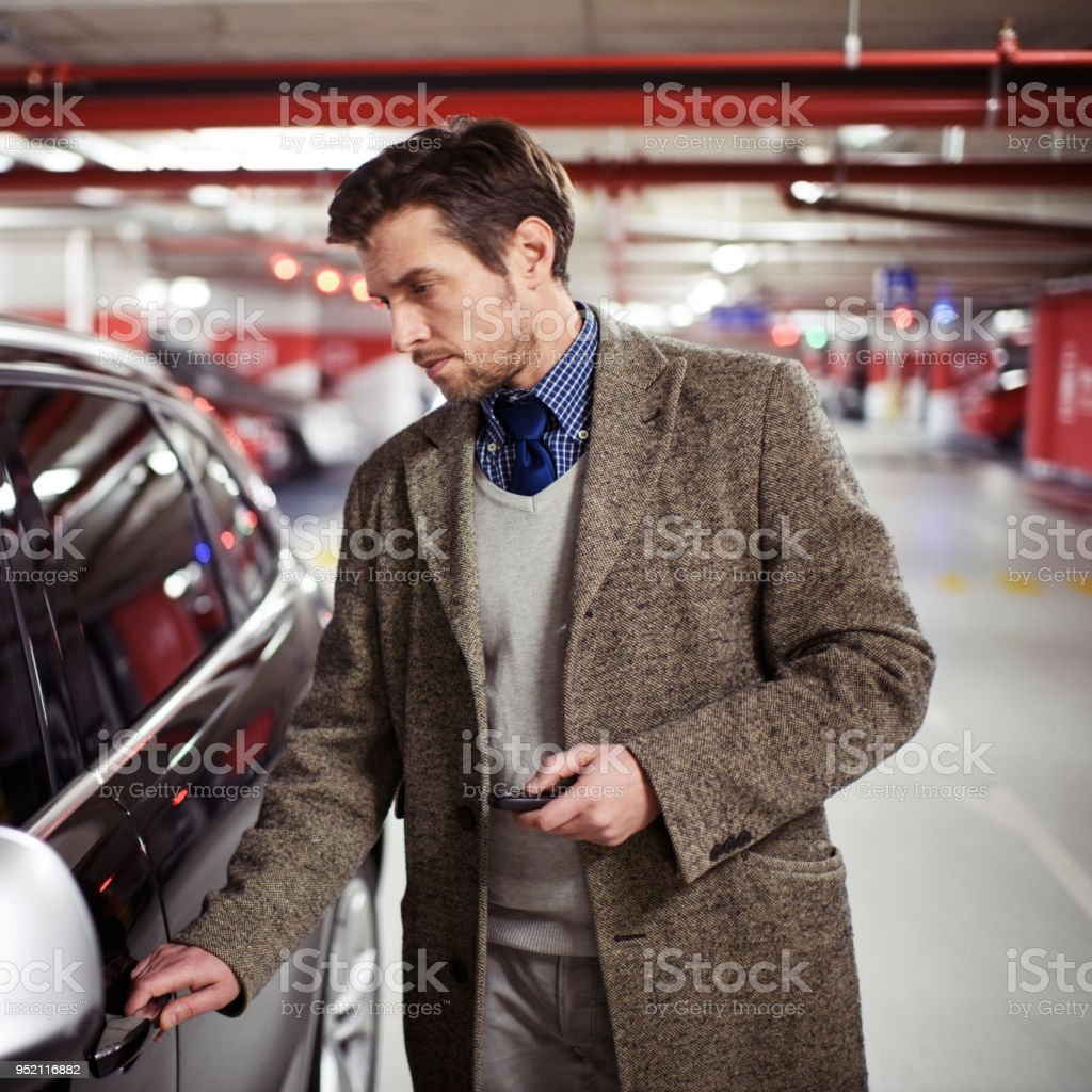 Elegant man standing inside the car garage and getting ready to enter...
