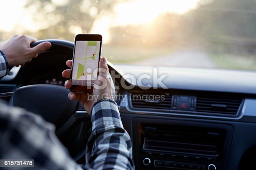 istock Man in the car holding mobile phone 615731478