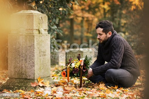 Mid adult man with flowers and candles visiting graves at the cemetery.