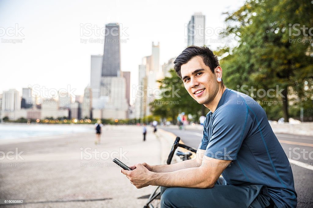 Man in the city street texting on the smartphone stock photo