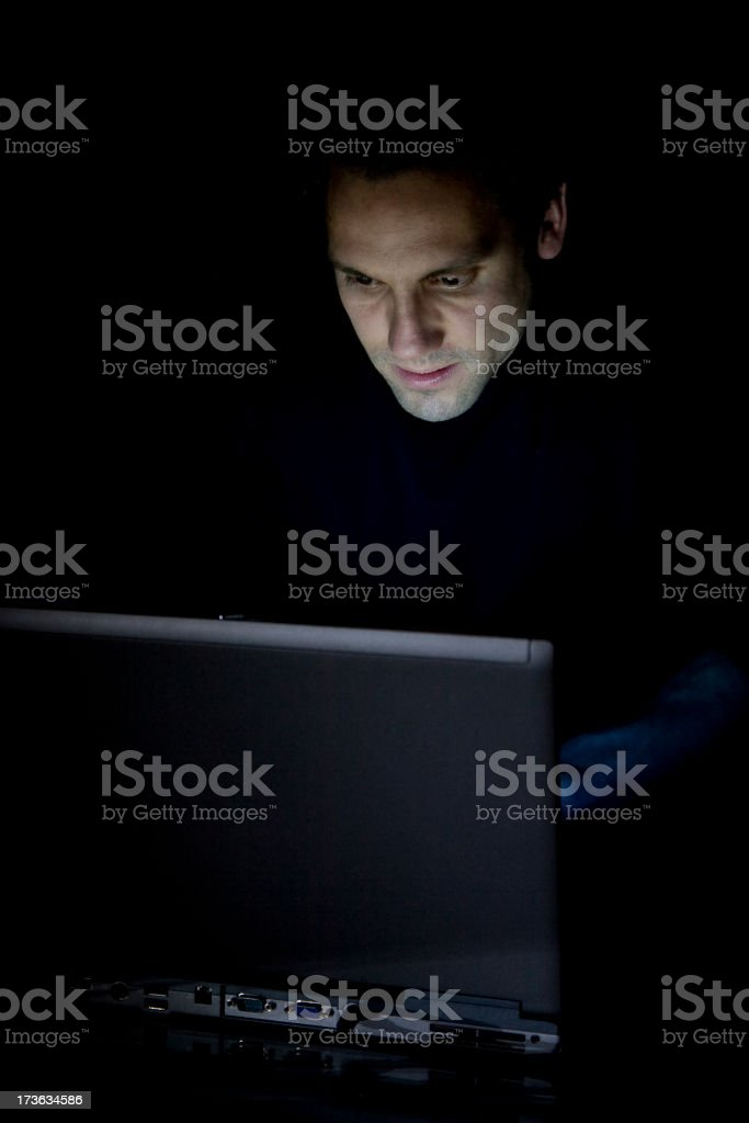 A man in the dark using a black laptop looking sneaky royalty-free stock photo