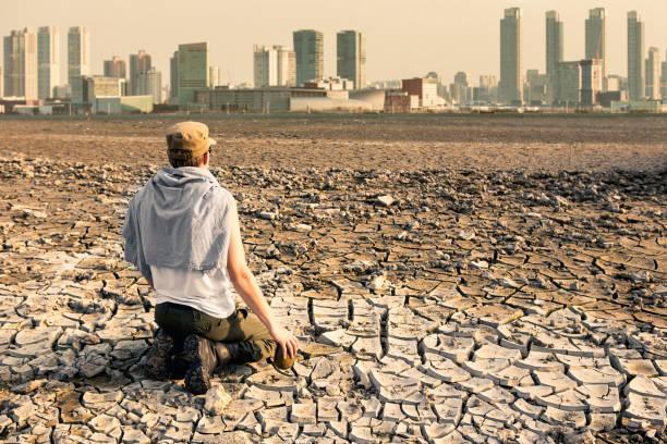 çölde bir adam küresel ısınma etkileri sonra şehre bakıyor - kuraklık stok fotoğraflar ve resimler