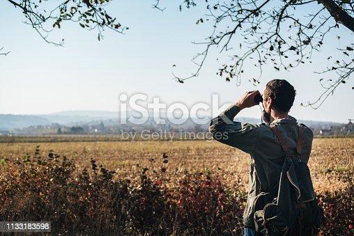 Man in the forest looks through binoculars