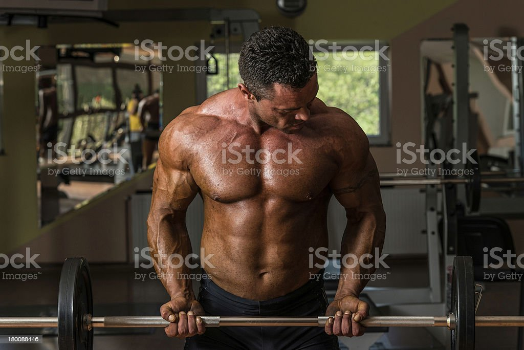 Man in the gym performing biceps curls with a barbell royalty-free stock photo