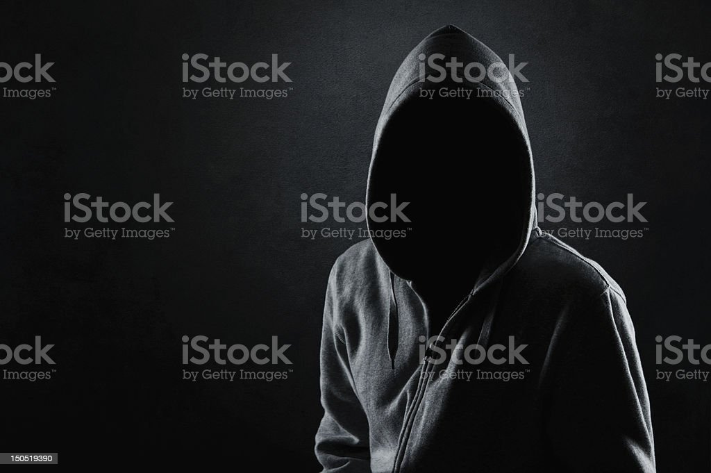 Man in the hood Silhouette of hooded man or hooligan over dark concrete background with copy space Adult Stock Photo