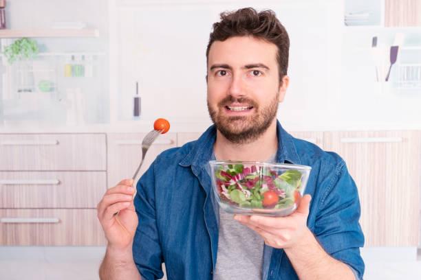 mann in der küche bereit, gemüse zu essen - abnehmen leicht gemacht stock-fotos und bilder