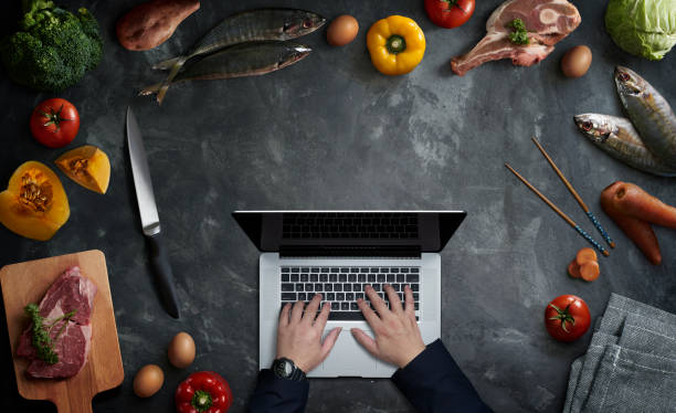 Man in the kitchen searching for recipes on his laptop stock photo