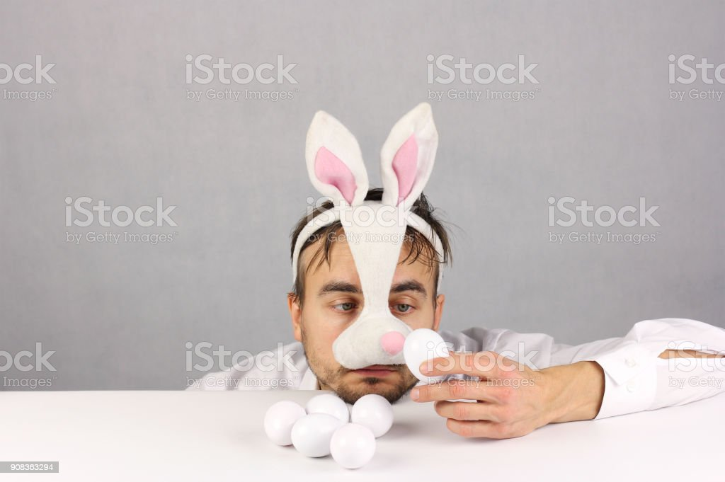 man in the mask Easter rabbit looking at the egg stock photo