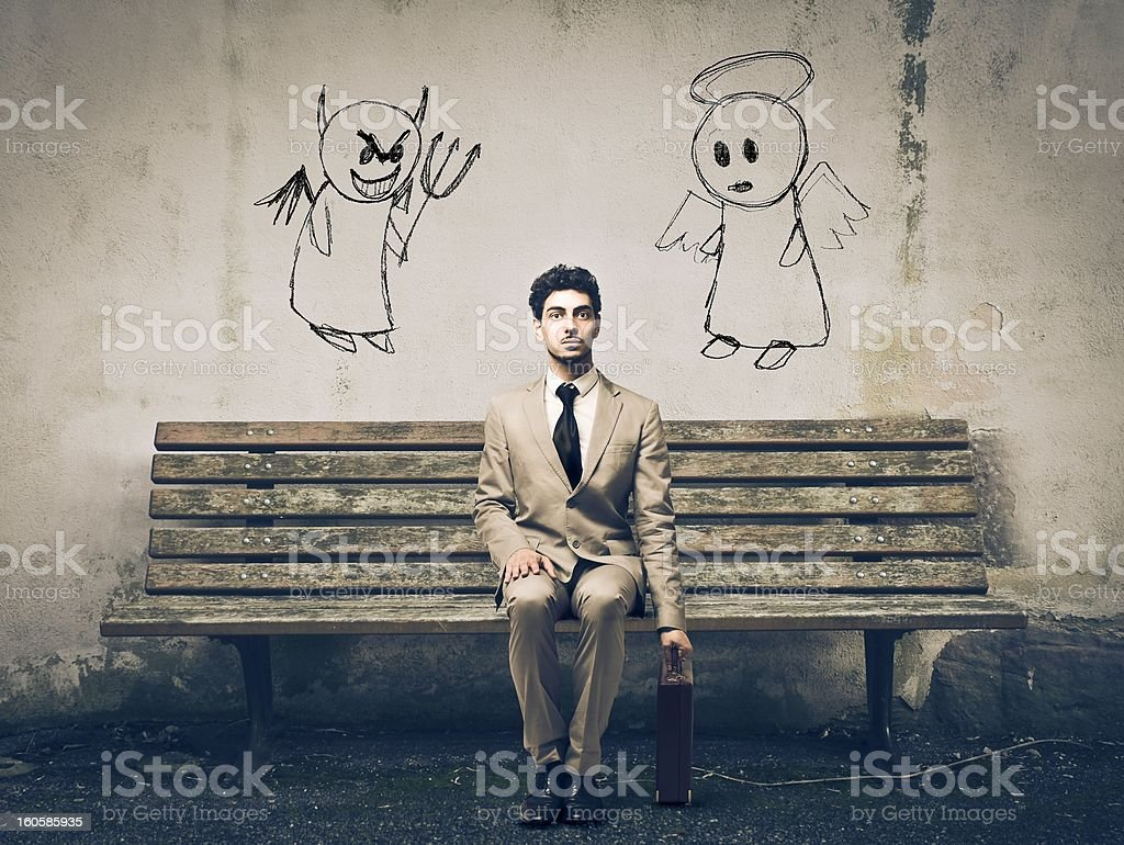A man in the middle of an angel and demon drawings stock photo