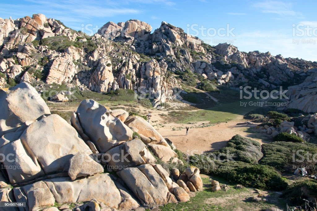 Man in the middle of valley with interesting rock formations stock photo