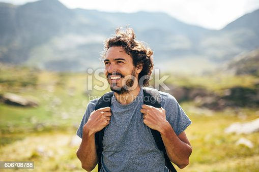 Happy male hiker standing in the beautiful mountain.