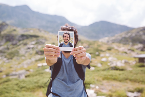 Man in the mountain showing instant photo