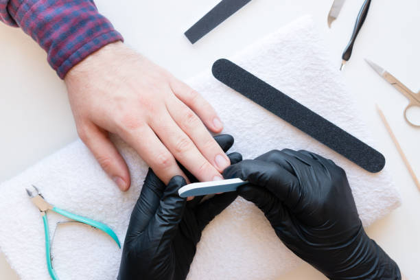 man in the nail salon makes a manicure man in the nail salon makes a manicure pedicure manicure men beauty spa stock pictures, royalty-free photos & images