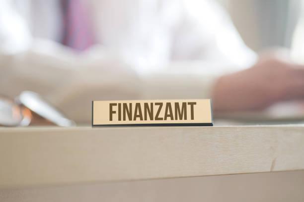 Ein Mann im Büro und Hinweis auf Finanzamt – Foto