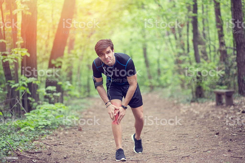 Man in the park with injured knee stock photo