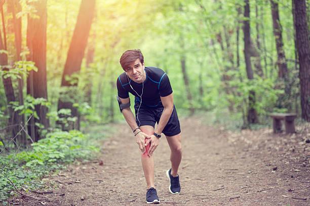 man in the park with injured knee - knäskål bildbanksfoton och bilder