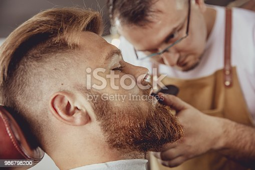 928445950 istock photo Man in the process of trimming a beard in a barbershop 986798200
