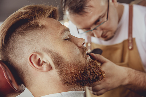 986804130 istock photo Man in the process of trimming a beard in a barbershop 986798200