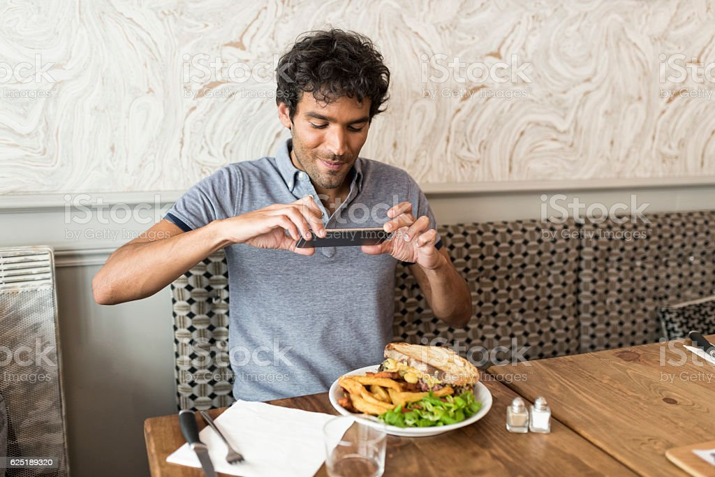 Man in the restaurant taking picture food with cell phone stock photo