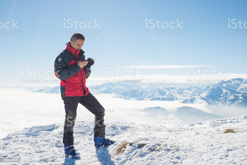 A man in the snow on his mobile stock photo