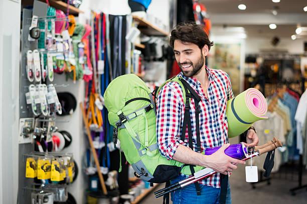 Uomo nel negozio di acquistare attrezzature da campeggio - foto stock