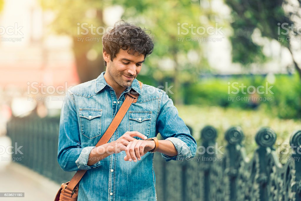 Man in the street using his smart-watch app. Urban background stock photo