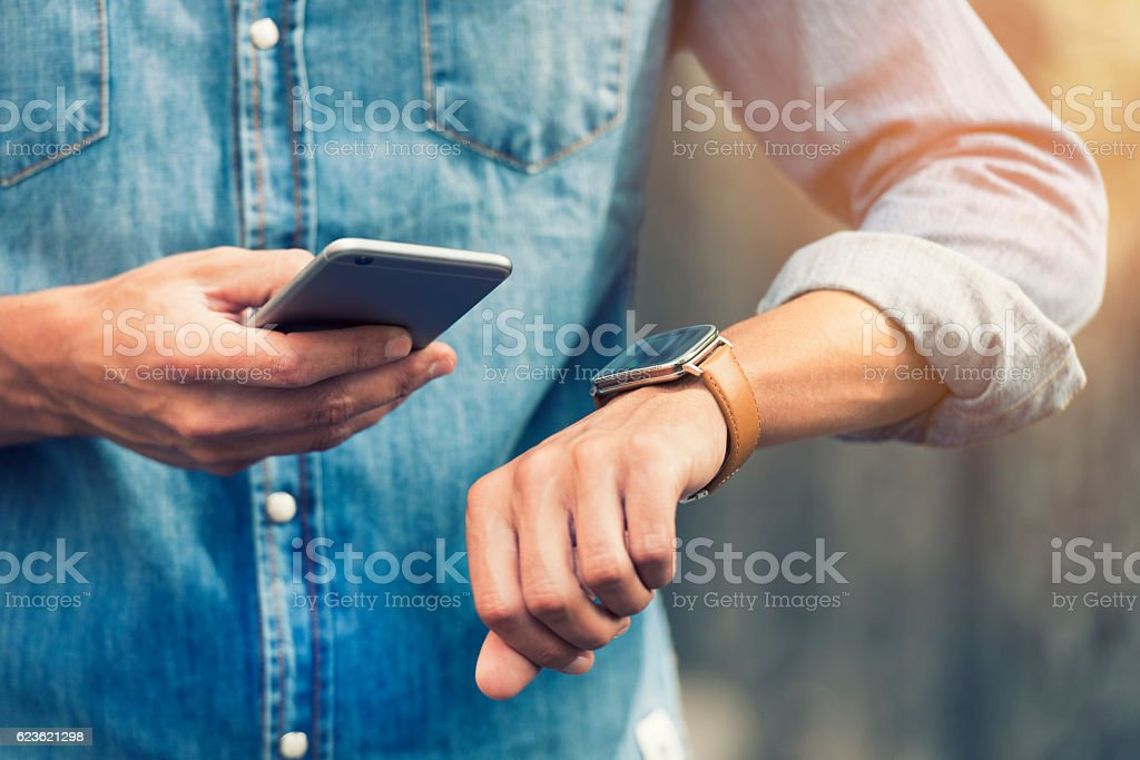 Man in the street with Mobile phone and smart watch stock photo
