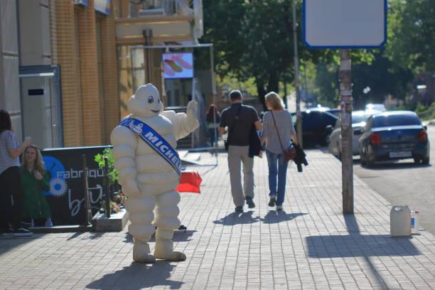 man in the suit of a bibendum on the street - mascotte photos et images de collection