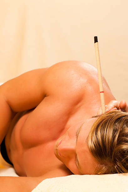 man in therapy with ear candles - hopi stock photos and pictures