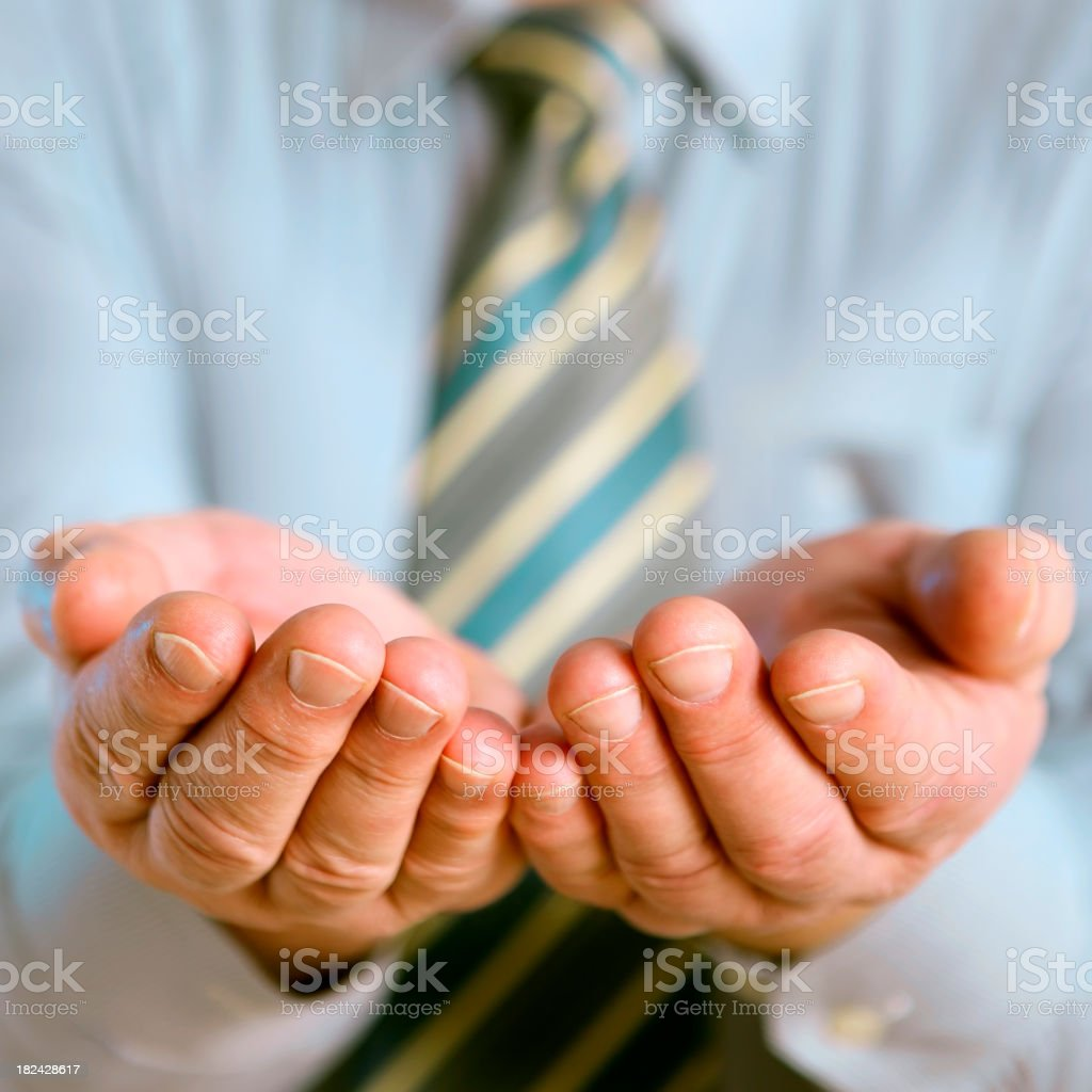 Man in tie holding out cupped hands royalty-free stock photo