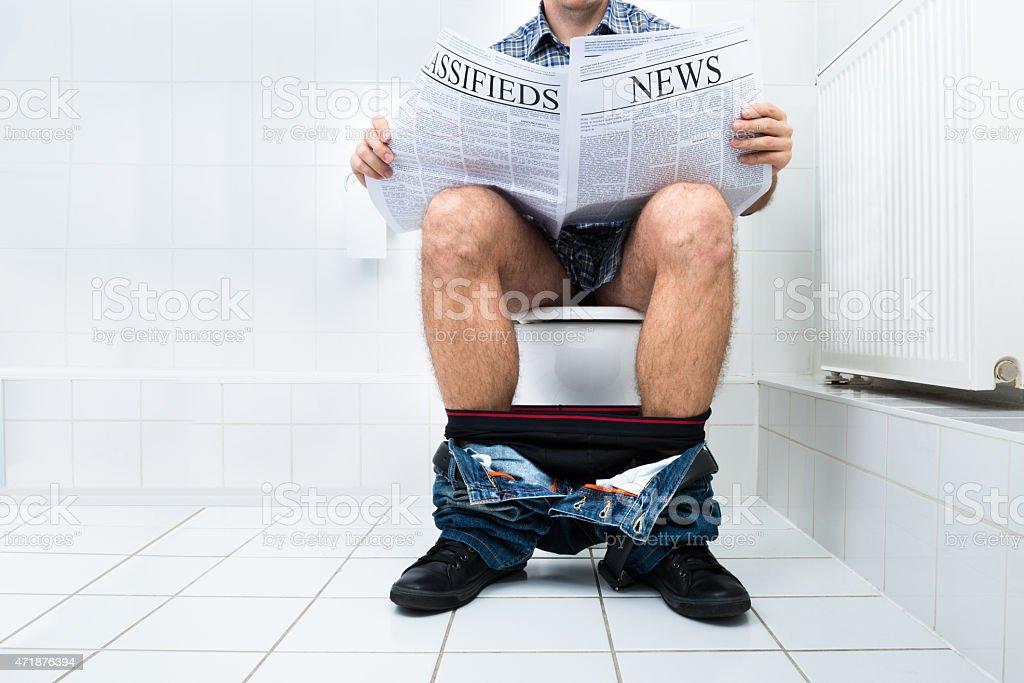 Man In Toilet Reading Newspaper stock photo