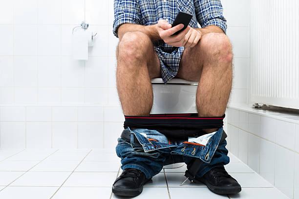 man in toilet using cellphone - cell phone toilet stockfoto's en -beelden