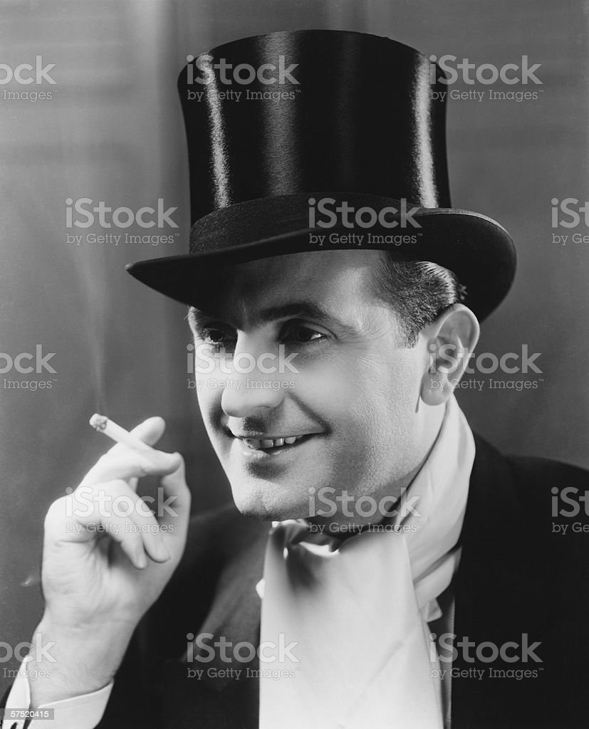 Man in top hat smoking cigarette, (B&W), portrait stock photo