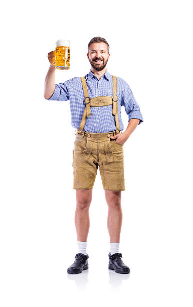 man in traditional bavarian clothes holding mug of beer - german culture stock pictures, royalty-free photos & images