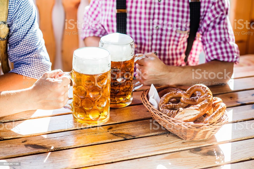 Man in traditional bavarian clothes holding mugs of beer - Photo