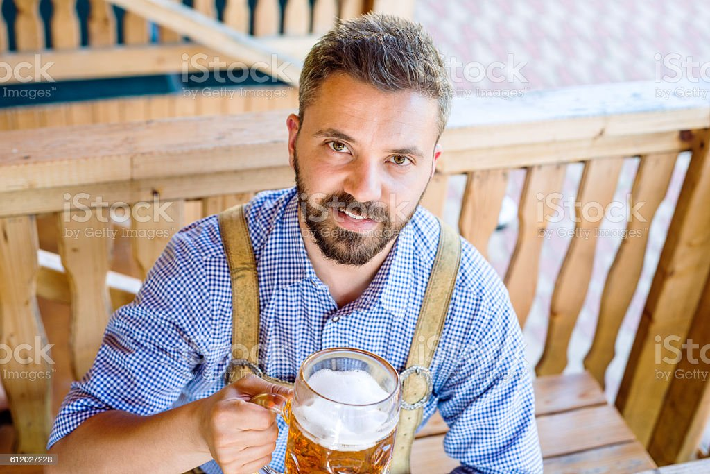 Man in traditional bavarian clothes with beer and pretzels – Foto
