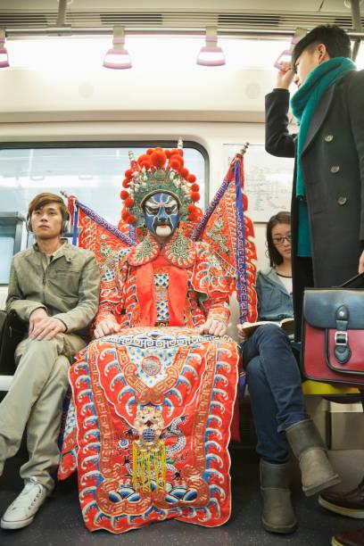 mann in der traditionellen chinesischen oper kostüm u-bahn fahren - festzugskleidung stock-fotos und bilder