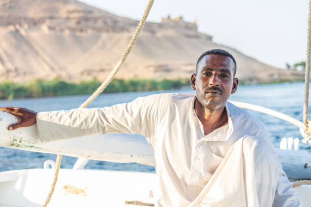 Man in traditional dress sailing a felucca boat on the Nile River stock photo