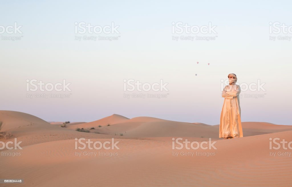 man in traditional outfit in a desert near Dubai stock photo